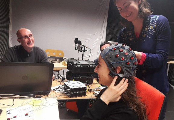 An EEG cap is being placed on the head of a subject by an experimenter on the right while another experimenter on the left is setting up the necessary software on the computer.